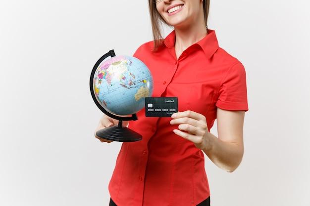 Przycięte zdjęcie nauczyciel biznesu kobieta w czerwonej koszuli okulary spódnica trzyma kulę ziemską i kartę kredytową na białym tle. nauczanie edukacji na uniwersytecie, turystyka, koncepcja studiów za granicą.