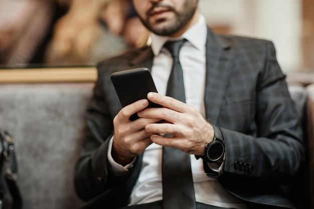 Przycięte zdjęcie odnoszącego sukcesy biznesmena za pomocą smartfona siedząc w fotelu w hotelowym holu, miejsce kopiowania