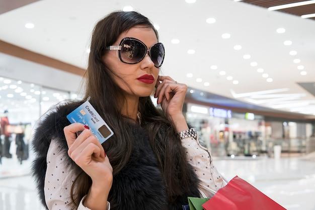 Przycięte zdjęcie pięknej dziewczyny z torby na zakupy i kartą kredytową robi zakupy w centrum handlowym. pretensjonalna modelka w okularach przeciwsłonecznych na tle supermarketu.