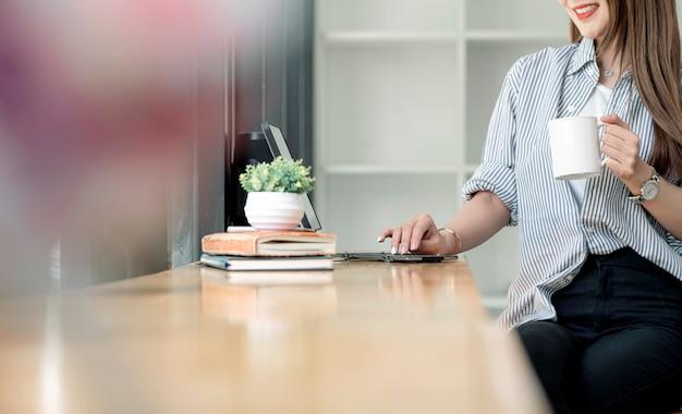 Przycięte zdjęcie pięknej kobiety azji gospodarstwa biały kubek i pracy na komputerze podczas pobytu w domu.