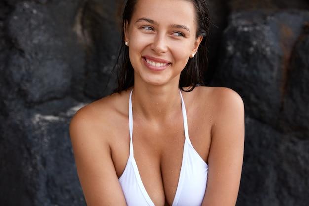 Przycięte zdjęcie pięknej uśmiechniętej młodej kobiety z doskonałymi piersiami