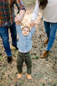 Przycięte zdjęcie plenerowe szczęśliwej rodziny w stylowych, codziennych ubraniach, bawiących się i bawiących się w jesiennym sosnowym lesie, trzymających się za ręce ich uroczego synka, latających w powietrzu