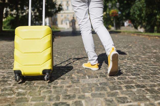 Przycięte zdjęcie podróżnika turystycznego kobiety nogi w żółtym letnim ubraniu z walizką spaceru w mieście na świeżym powietrzu. dziewczyna wyjeżdża za granicę na weekendowy wypad. styl życia podróży turystycznej.