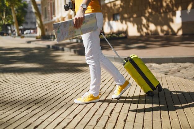 Przycięte zdjęcie podróżnika turystycznego kobiety w żółtym ubraniu z mapą miasta walizka spaceru w mieście na świeżym powietrzu. dziewczyna wyjeżdża za granicę na weekendowy wypad. koncepcja życia podróż turystyka.