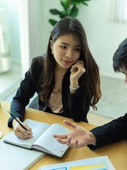 Przycięte zdjęcie pracowniczki biurowej pracującej ze współpracownikiem nad projektem w sali konferencyjnej