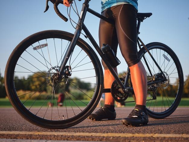 Przycięte zdjęcie profesjonalnego kolarza płci męskiej w spodenkach rowerowych i butach stojących z rowerem