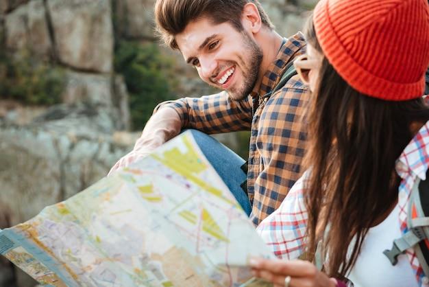 Przycięte zdjęcie przedstawiające adwentową parę z mapą w pobliżu kanionu