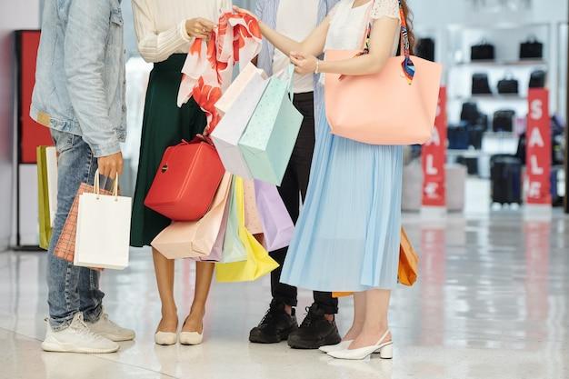 Przycięte zdjęcie przedstawiające młodych ludzi z torbami na zakupy, pokazujących sobie nawzajem, co kupili w czarny piątek