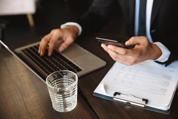 Przycięte zdjęcie przystojny młody biznesmen siedzi w kawiarni przy użyciu komputera przenośnego, trzymając schowka za pomocą telefonu.