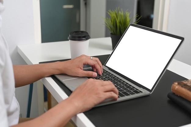 Przycięte zdjęcie rąk człowieka, wpisując na komputerze przenośnym przy biurku.