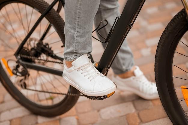 Przycięte zdjęcie rowerzysty rasy kaukaskiej w sportowych butach, pedałującej po wyłożonej płytkami ścieżce rowerowej