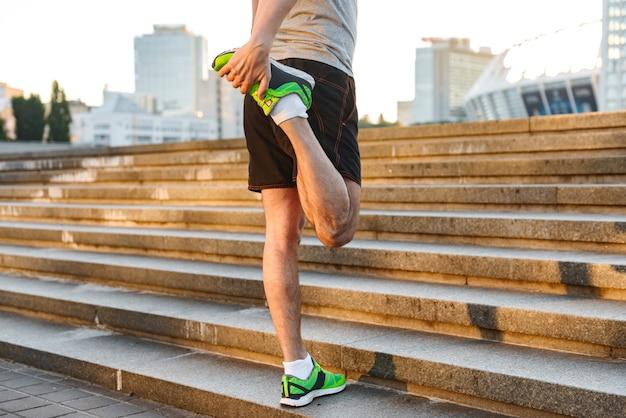 Przycięte zdjęcie sportowca rozciągającego nogi
