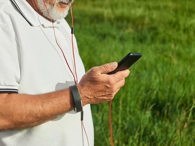 Przycięte zdjęcie starego człowieka sprawdzania czasu podczas biegania na zewnątrz.