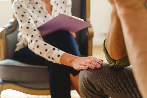 Przycięte zdjęcie starszej psychoterapeutki pracującej z kaukaskim pacjentem płci męskiej w jej gabinecie