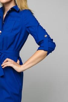Przycięte zdjęcie stockowe jasnowłosej kobiety bez twarzy, noszącej formalną jasną sukienkę w kolorze indygo z 3 4-rękawami.