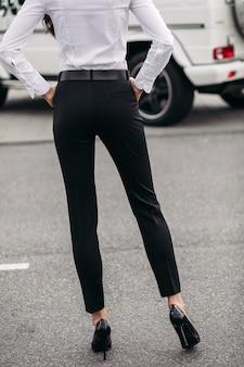 Przycięte zdjęcie stockowe nierozpoznawalnej kobiety w białej koszuli i formalnych czarnych prostych spodniach i czarnych skórzanych obcasach, stojącej na ulicy. modelka. koncepcja dresscode.