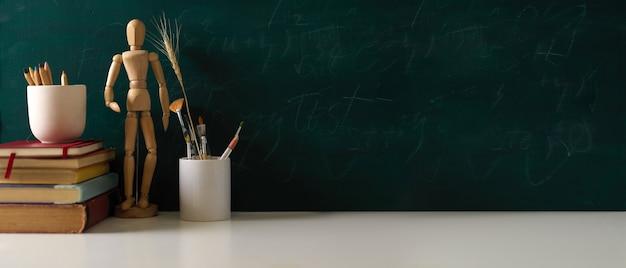 Przycięte zdjęcie stołu do nauki z książkami miejsca do kopiowania narzędzi do malowania i drewnianej figury w tle ściany tablicy