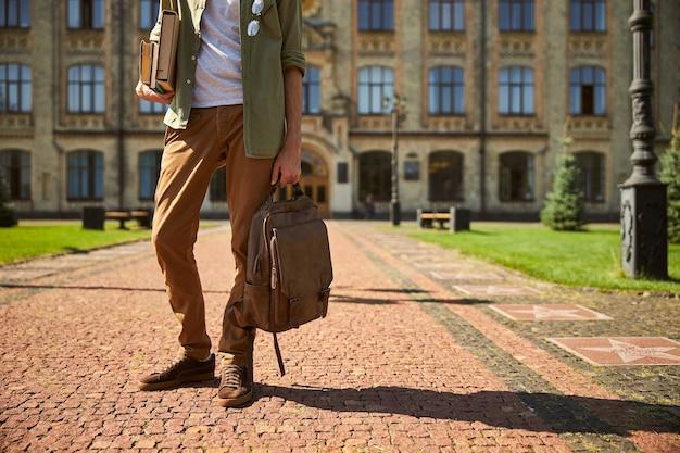Przycięte zdjęcie studenta płci męskiej stojącego na ceglanym chodniku przed budynkiem uniwersytetu