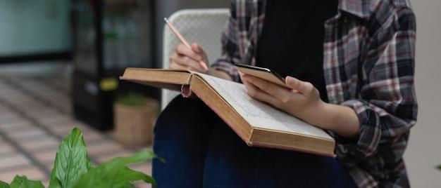 Przycięte zdjęcie studentki przy użyciu smartfona do wyszukiwania informacji podczas czytania książki w ogrodzie