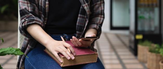 Przycięte zdjęcie studentki relaks przed czytaniem książki ze smartfonem, siedząc na podwórku