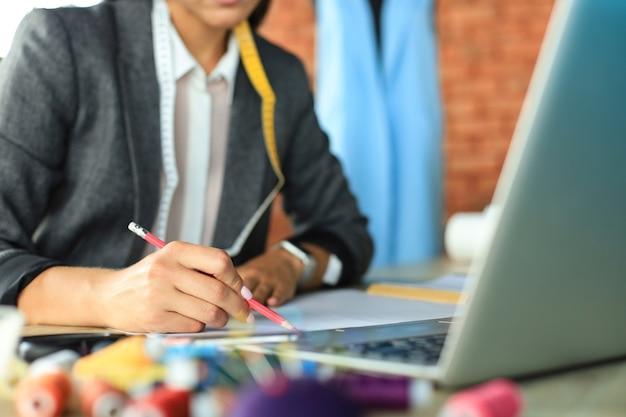 Przycięte zdjęcie stylowego projektanta mody pracy z laptopem i rysunek szkicu w atelier.