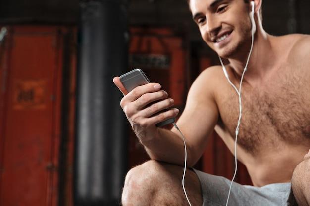 Przycięte zdjęcie szczęśliwego człowieka siedzącego na siłowni podczas słuchania muzyki przez telefon.