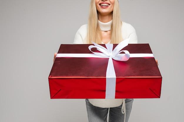 Przycięte zdjęcie szczęśliwej kobiety w białym swetrze z dużym pudełkiem