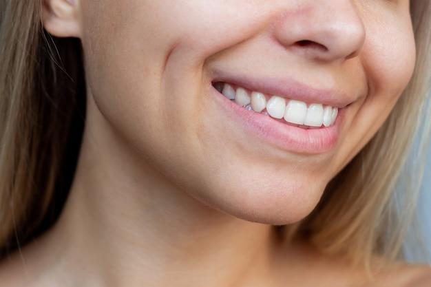 Przycięte zdjęcie twarzy młodej, uśmiechniętej blond kobiety rasy kaukaskiej z dołeczkami na policzkach