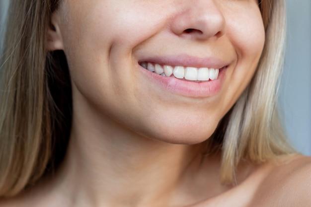 Przycięte zdjęcie twarzy młodej uśmiechniętej blondynki z dołeczkami na policzkach stomatologia