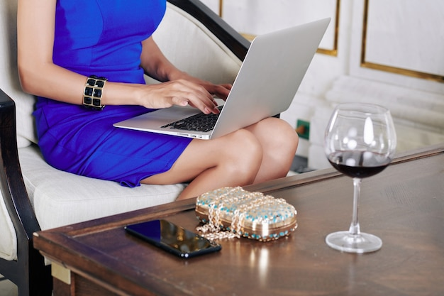 Przycięte zdjęcie ubrana młoda kobieta pije kieliszek wina i pracuje na laptopie