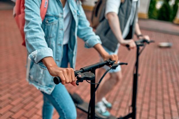 Przycięte zdjęcie uczniów jadących na skuterach elektrycznych.