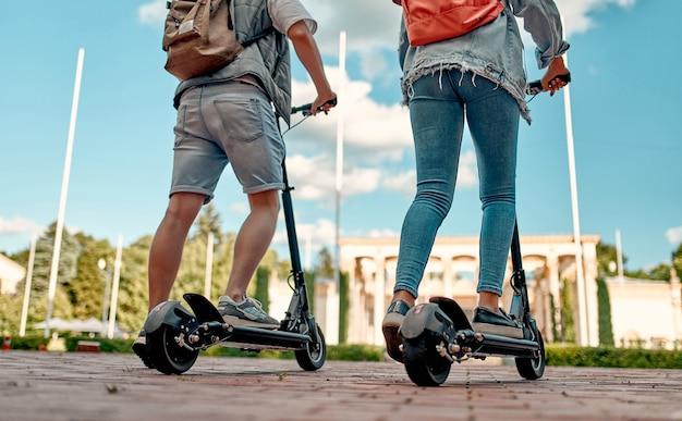 Przycięte zdjęcie uczniów jeżdżących na skuterach elektrycznych. facet i dziewczyna na skuterach jadą miejską drogą.