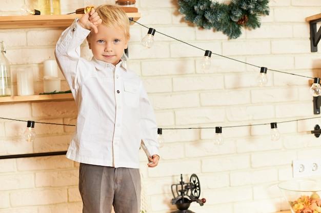 Przycięte zdjęcie uroczego blondyna europejskiego dziecka płci męskiej w białej koszuli pozującego boso w kuchni, stojącego na blacie, wyrażającego niechęć lub negatywną reakcję, pokazującego kciuk w dół