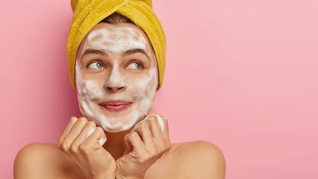 Przycięte zdjęcie uroczej młodej kobiety myje twarz pieniącym się mydłem, ma zadowolony wyraz twarzy, trzyma ręce razem pod brodą, ma poranny rutynę