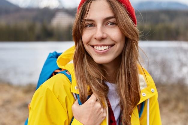 Przycięte zdjęcie uroczej, wesołej europejki ma szeroki, czuły uśmiech, długie proste włosy i nosi czerwony kapelusz