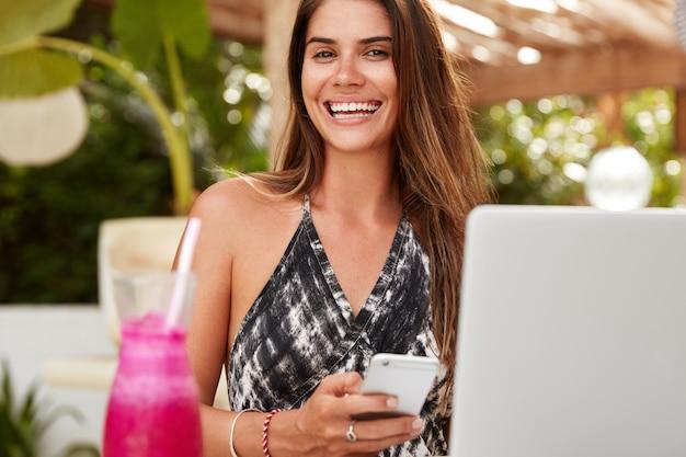 Przycięte zdjęcie wesoła brunetka czyta powiadomienie przychodzące na smartfonie