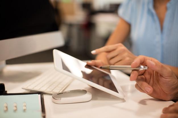 Przycięte zdjęcie współpracowników omawiających na cyfrowym tablecie