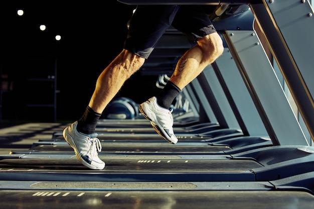 Przycięte zdjęcie wysportowanego mężczyzny w stroju sportowym biegnącego na bieżni w sali gimnastycznej z naciskiem na nogi