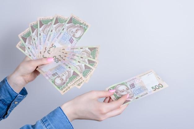 Przycięte zdjęcie z bliska damskich rąk trzymających stos pieniędzy, aby skopiować przestrzeń na białym tle szarym tle
