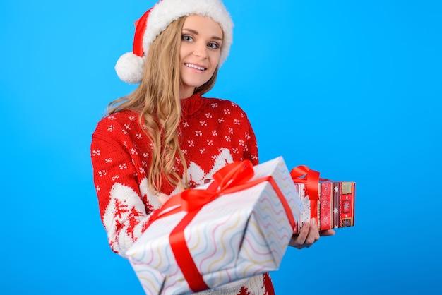 Przycięte zdjęcie z bliska dużego ładnego pudełka prezentowego z czerwoną kokardą, piękna kobieta ubrana w czerwony sweter z dzianiny daje prezent pudełko na białym tle na jasnoniebieskim tle
