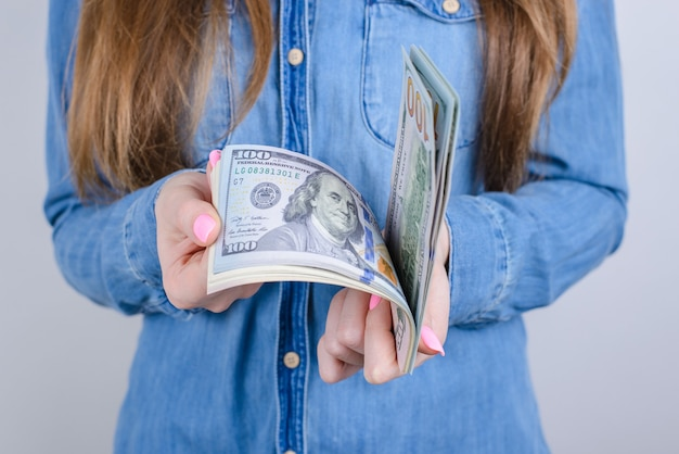 Przycięte zdjęcie z bliska dziewczęce piękne dłonie z długimi paznokciami różowy jasny manicure na palcach trzymających obliczanie starych pieniędzy w dżinsowych ubraniach na białym tle szarym tle