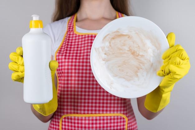 Przycięte zdjęcie z bliska nieszczęśliwej zdenerwowanej smutnej matki używającej chemicznego detergentu, ale marzącej o nowej zmywarce na białym tle szarym tle