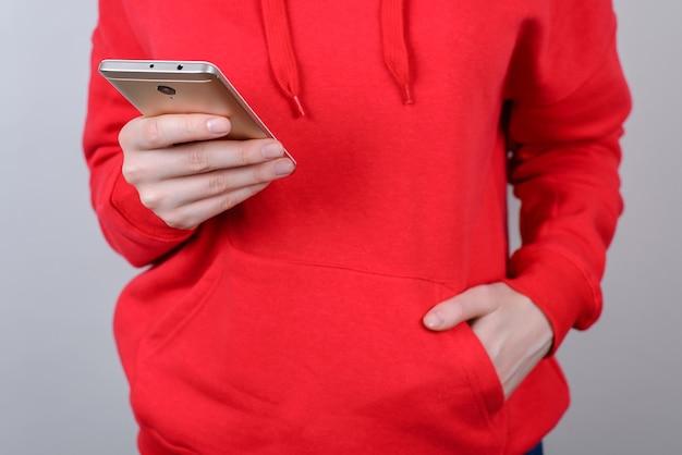 Przycięte zdjęcie z bliska osoby trzymającej kształtujące posty komentuje w internecie komórkowym na białym tle szarym tle
