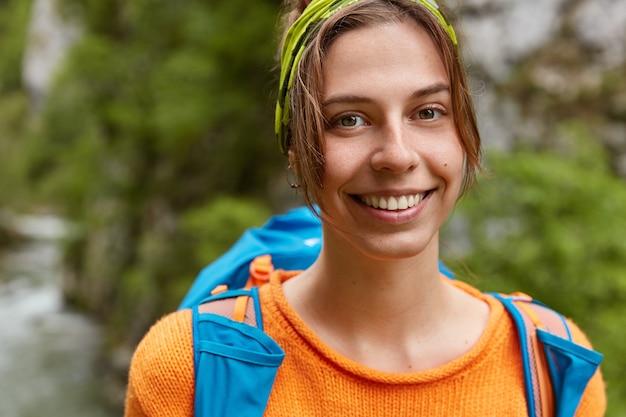 Przycięte zdjęcie zadowolonej kobiety uśmiecha się delikatnie, ma wycieczkę z plecakiem