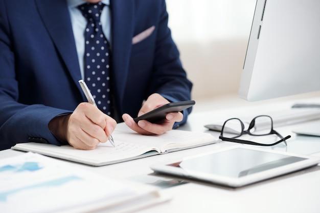 Przycięty biznesmen robienia notatek ze swojego kalendarza smartfona do organizatora