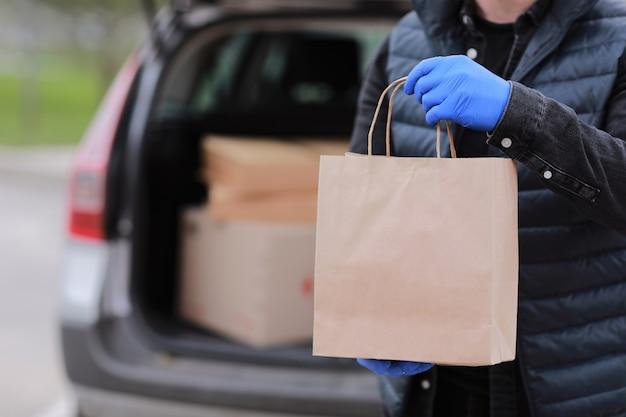 Przycięty dostawca w rękawiczkach trzyma papierową torbę w pobliżu samochodu na zewnątrz