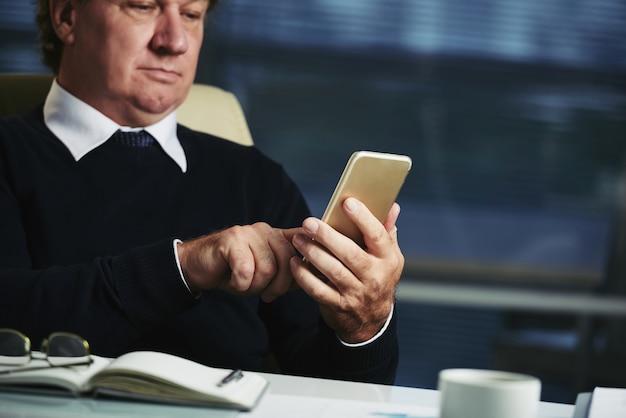 Przycięty dżentelmen sprawdzający wiadomości na swoim smartfonie