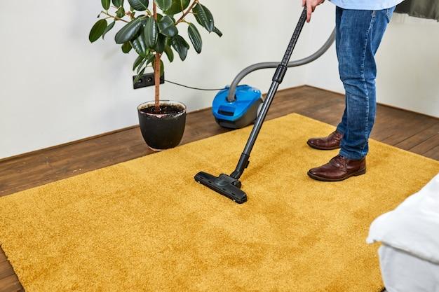 Przycięty mężczyzna czyści dywan podłogowy za pomocą odkurzacza w nowoczesnym białym salonie
