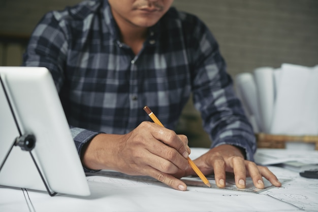 Przycięty mężczyzna szkicowania projektu budowlanego ołówkiem