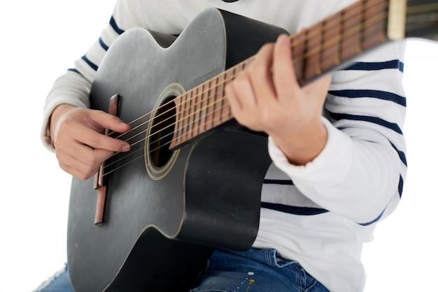 Przycięty nierozpoznawalny mężczyzna gra na gitarze akustycznej